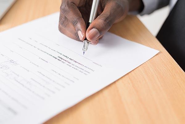 Homme qui signe un document